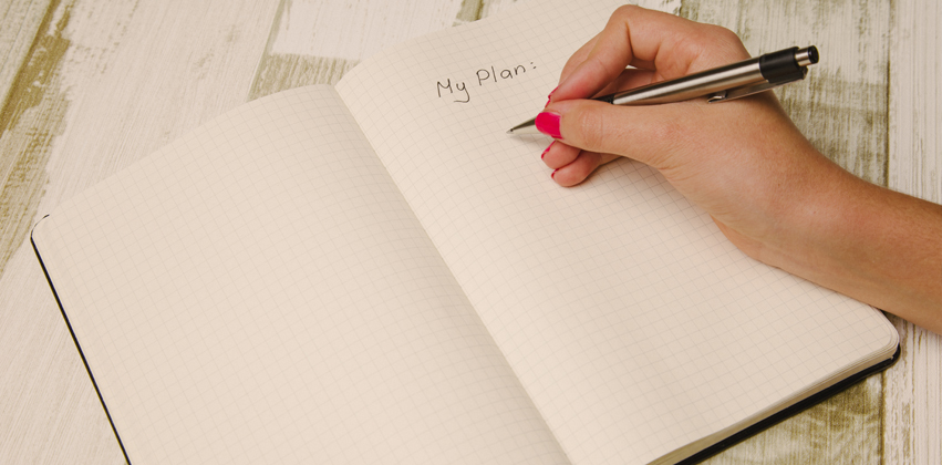 Woman writing in notebook page titled my plan