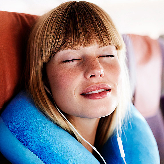 Blonde women resting on an airplane with earbuds in