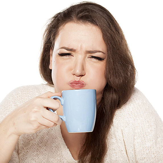 Brunette woman drinking coffee and making a face
