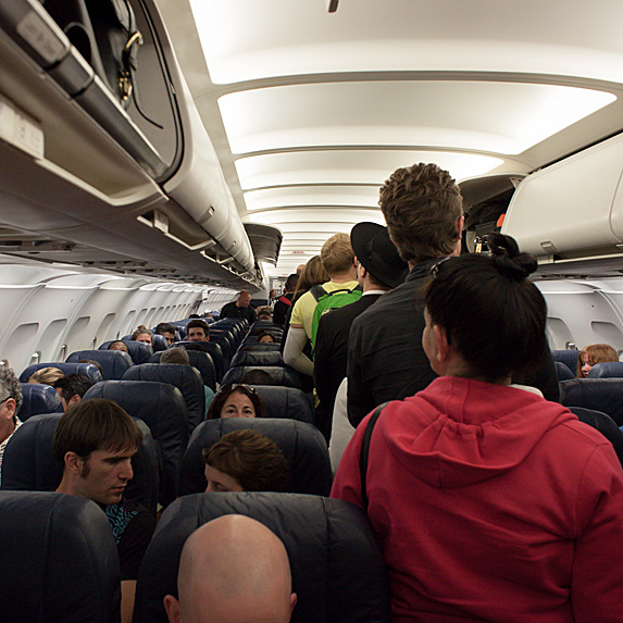 Passengers boarding a plane and storing their carry-on luggage