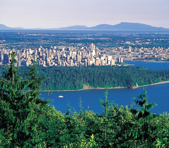Aerial shot of Stanley Park's lush forest and distant city views in Vancouver on a sunny day