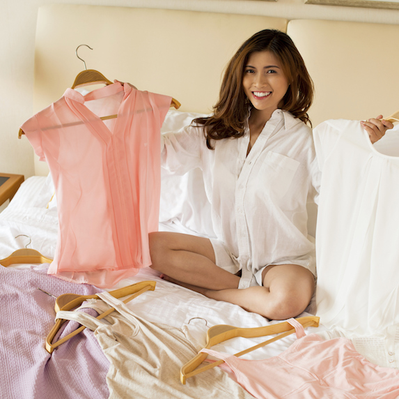 Smiling brunette woman sits on bed holding up different blouses on hangers in each hand