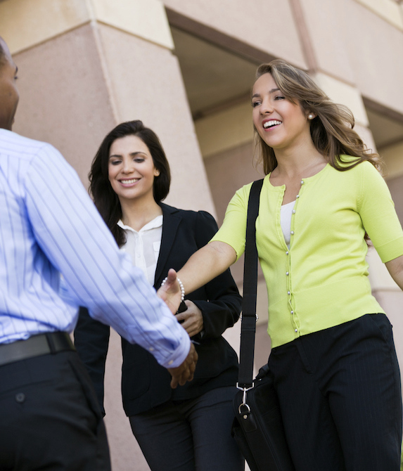 Smiling blonde woman in a yellow cardigan reaches over to shake hands with a man while her colleague, a smiling brunette woman in a dark suit and white blouse, looks on