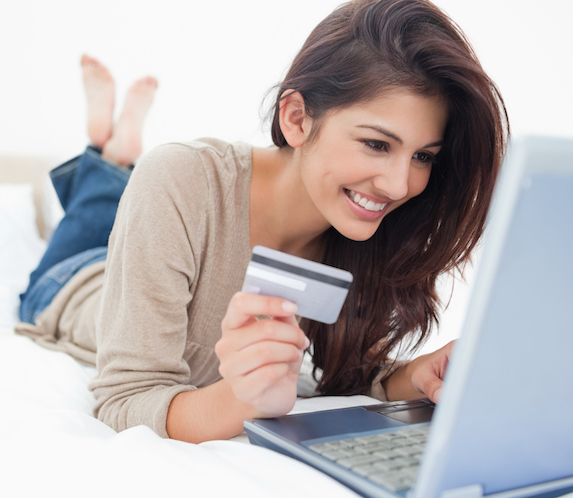 Young, smiling brunette in a tan blouse and blue jeans lies on her bed holding her credit card in one hand while online shopping on her laptop