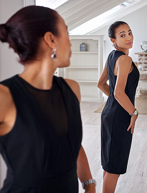 Woman looks back at the mirror while trying on an elegant black dress