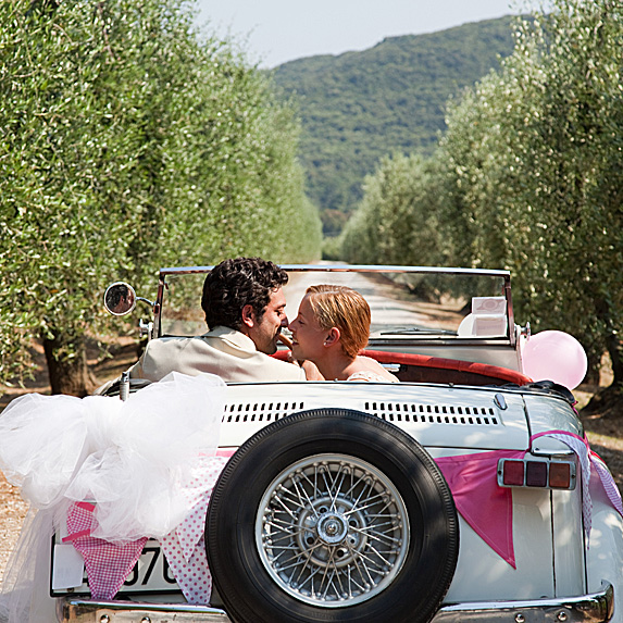Rear view of a young couple driving through an orchard and snuggling after wedding in a white vintage car