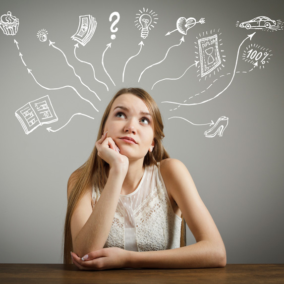 Young woman with long hair sits at a desk, leaning her chin against her hand and looking upwards, where images of things like money, cars and food have been drawn to signify her many trains of thought