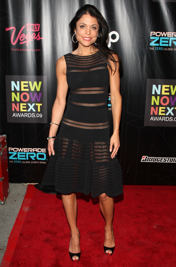 Reality TV star Bethenney Frankel poses on the red carpet in a sheer-paneled black dress with a swing skirt, open-toed black shoes and hoop earrings