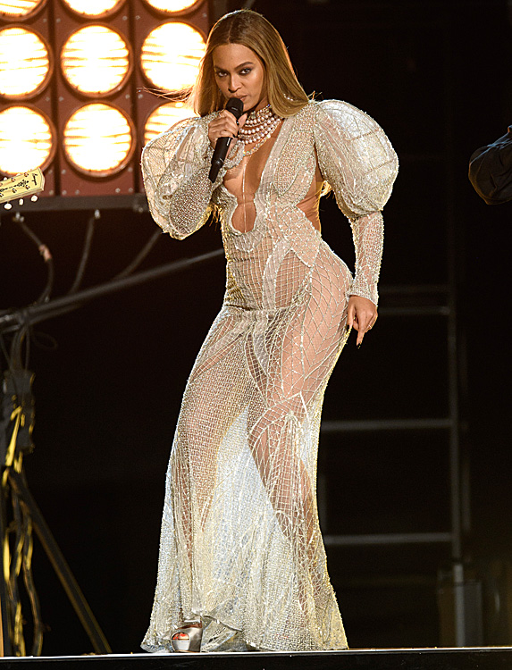 Singer Beyonce stands on stage holding a mic to her mouth as she performs in a floor-length sheer white gown heavily detailed with jewels and pearls