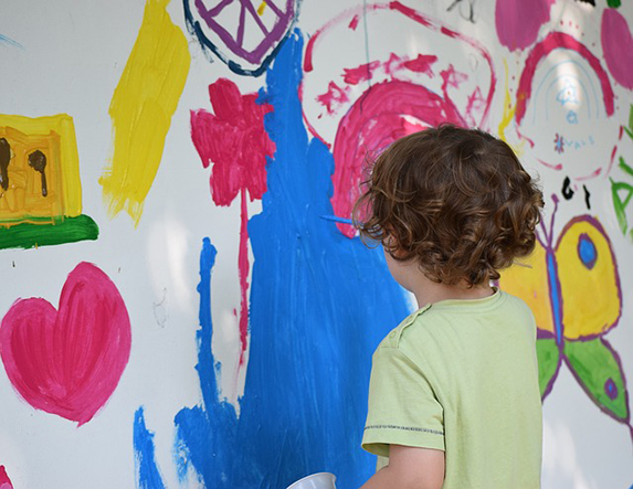 A young child painting a colourful mural on the wall.