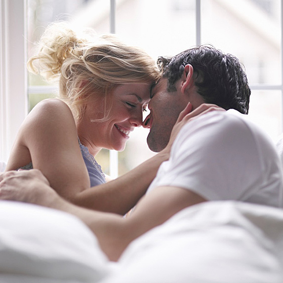Woman and man smiling in bed