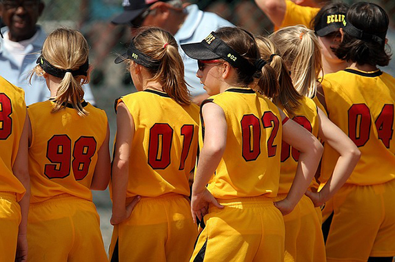 Lineup of young girls wearing yellow sports jerseys at a team sporting event.