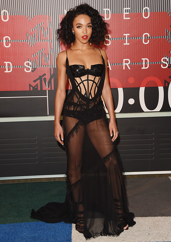 Singer FKA Twigs poses in a lingerie style black sheer gown with a sequin bra