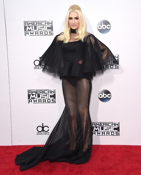 On an American Music Awards red carpet, Gwen Stefani poses in a sheer-detail black gown, with a peplum waist and voluminous overlay