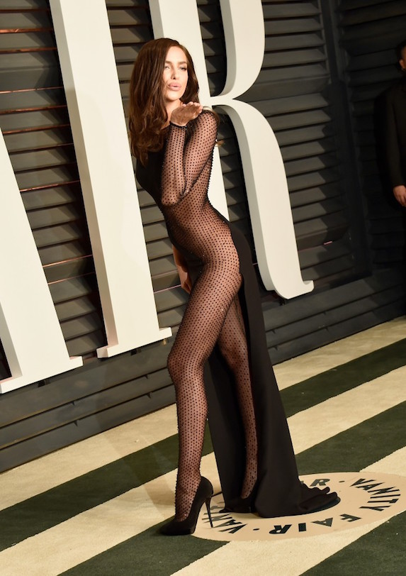 Model Irina Shayk poses at a Vanity Fair after-party in a black sheer and bejeweled jumpsuit, blowing kisses to photographers and onlookers
