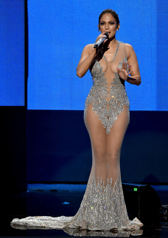 Jennifer Lopez stands on stage, speaking through a mic in hand, wearing a predominantly sheer floor-length gown with jeweled detailing in places for strategic coverage