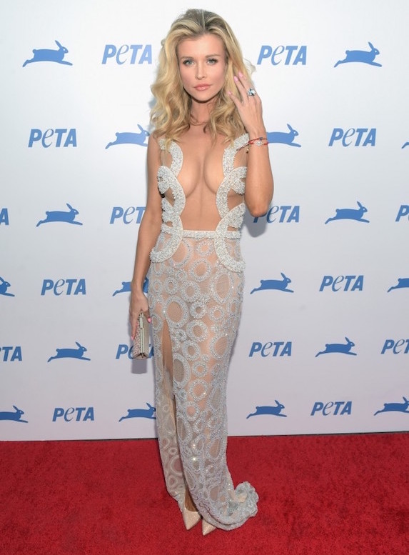 Joanna Krupa poses on a red carpet at an event for PETA wearing a sheer gown with circular embroidery details and a small cream-coloured clutch to match her pumps