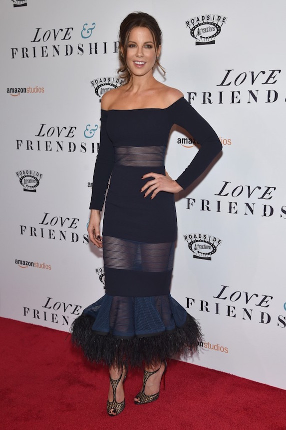 Kate Beckinsale poses with one hand on her hip in a dark blue, off-the-shoulder gown with sheer panels and a mermaid skirt with feather detail