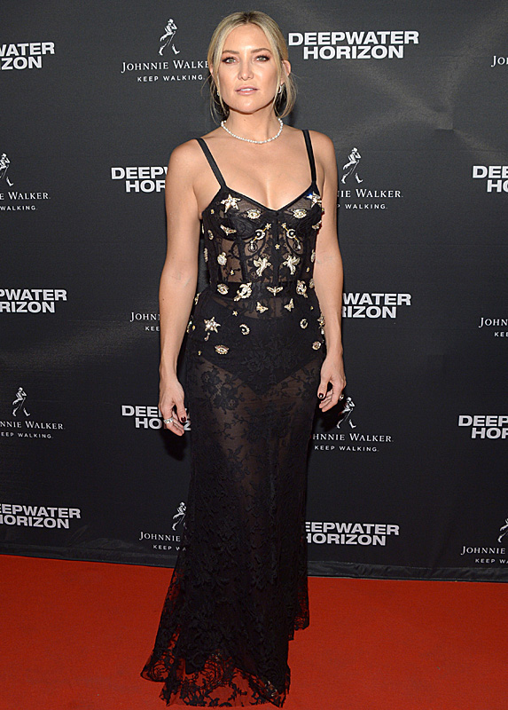 Actress Kate Hudson poses in a spaghetti strap black gown with sheer fabric and embroidered details