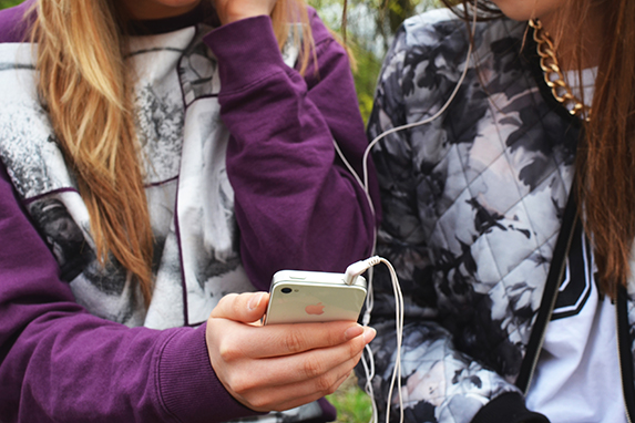 Two teenaged girls looking at a cell phone and listening to music in shared earphones.