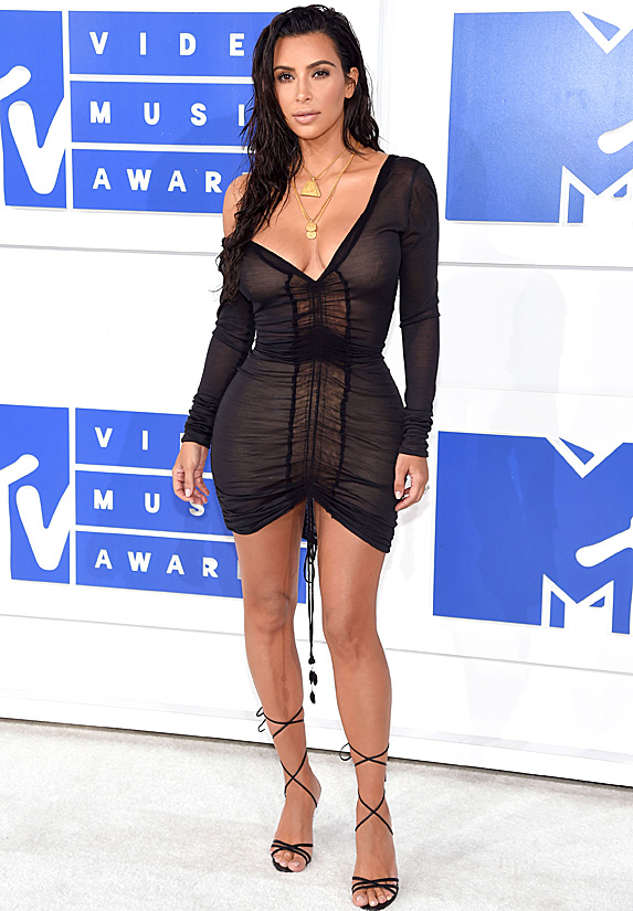 Kim Kardashian takes the red carpet for MTV in a sheer and ruched black mini dress, paired with strappy sandals, gold jewellery and wet-styled hair