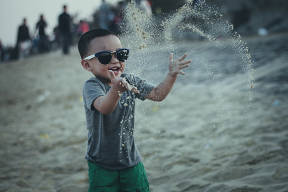 A young boy on the beach wearing sunglasses and throwing sand in the air.