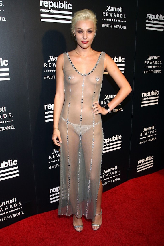 Singer Maty Noyse poses with her hand on her hip in a completely sheer gown with small jewel details and metallic pumps