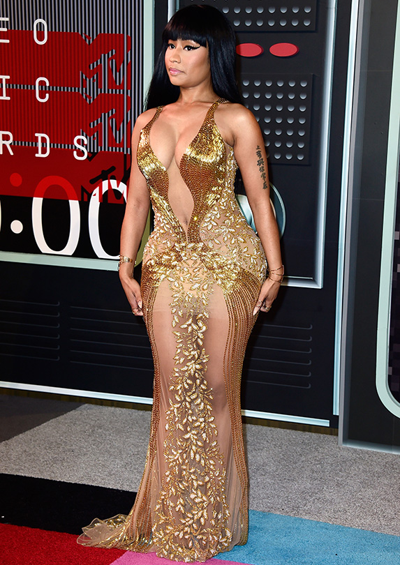 Nicki Minaj poses in a fitted sheer gown with gold sequin detail and a plunging neckline
