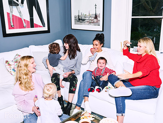 Group of women and their young children sitting around on white sofas chatting and laughing.