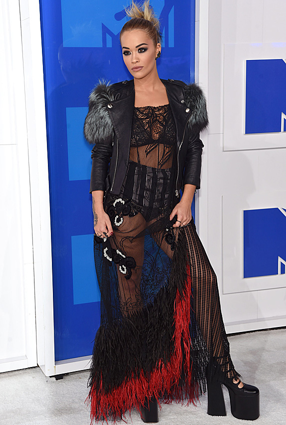 Singer Rita Ora poses in a black sheer and feather-detail gown with black high-waist briefs underneath, a leather jacket and chunky black platform boots