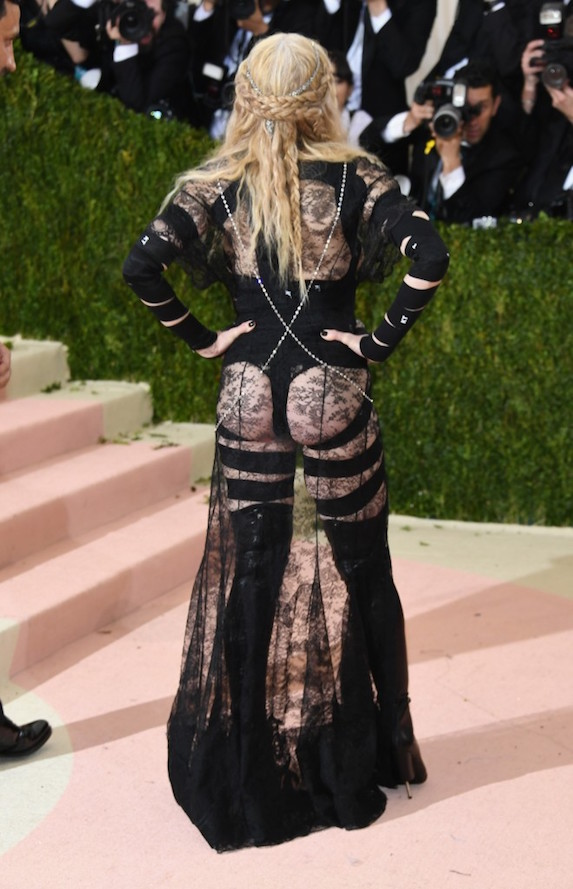 A scandalous rear view of Madonna posing with her hands on her hips at the 2016 Met Gala wearing a sheer ensemble with bondage style detailing and lace fabric