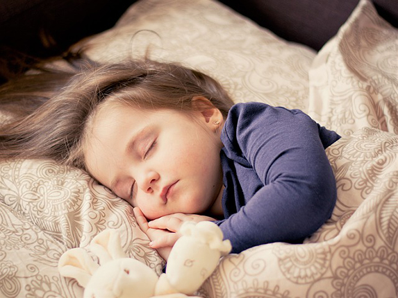 Toddler girl sound asleep next to a soft toy bunny.