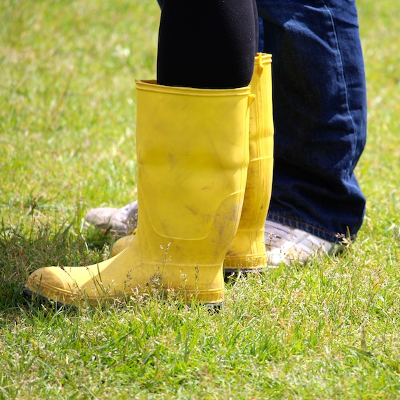 Yellow rubber boots on grass
