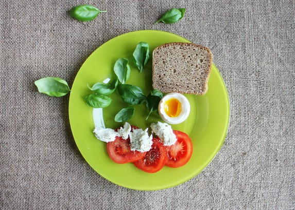 A plate with a hard boiled egg, whole grain bread, tomatoes. soft cheese and basil leaves.