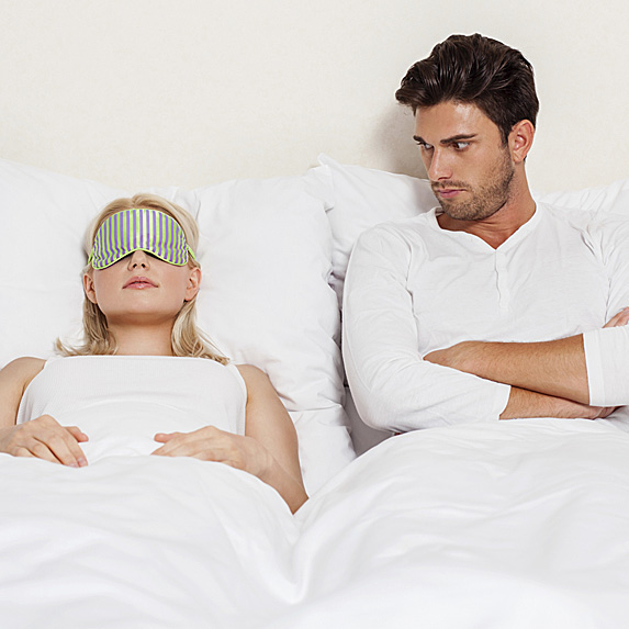 Woman sleeping while man stares angrily at her