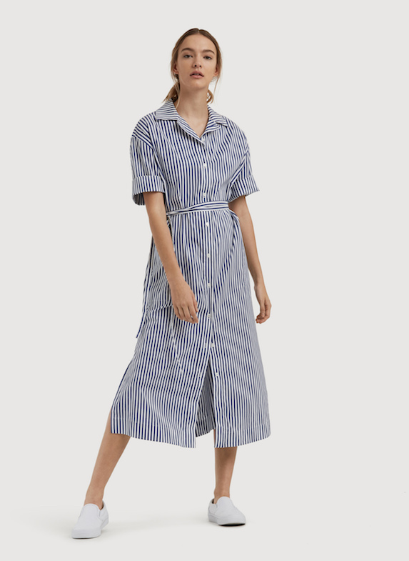 Model wears blue and white striped poplin shirt dress in a midi-length with white sneakers.