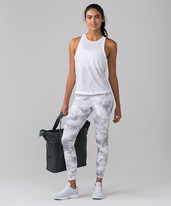 Model wearing white and grey print leggings with white running shoes