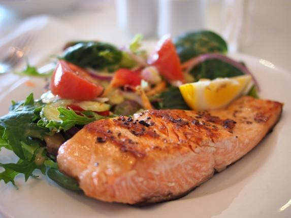 A prepared meal of grilled salmon and vegetables on a white plate.