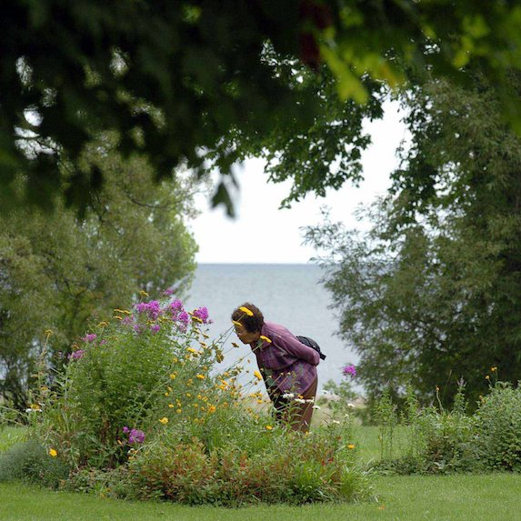 Woman smelling flowers in Cobourg, Ontario