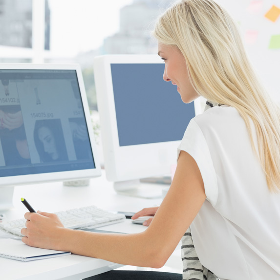 A blonde woman works at a computer desktop