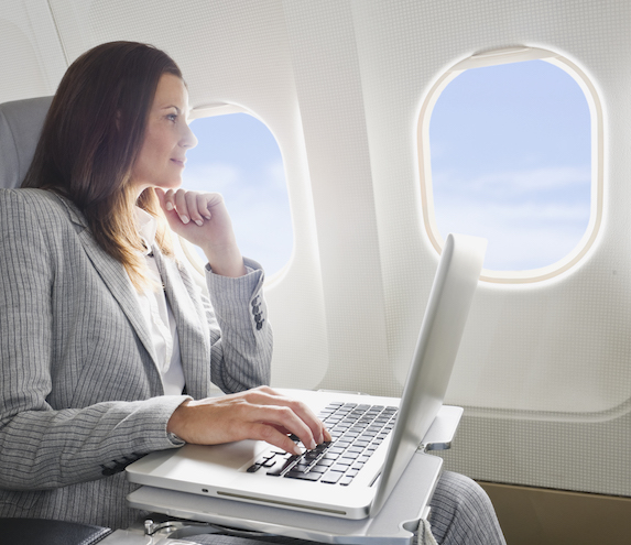 Businesswoman sitting on a plane looks out the window while her laptop sits open in front of her