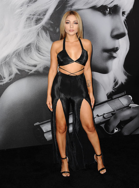 Actress Josephine Ochoa on a red carpet film premiere wearing a black two-piece outfit consisting of a bikini-style top and wide leg trousers with high slits cut in the front of each leg