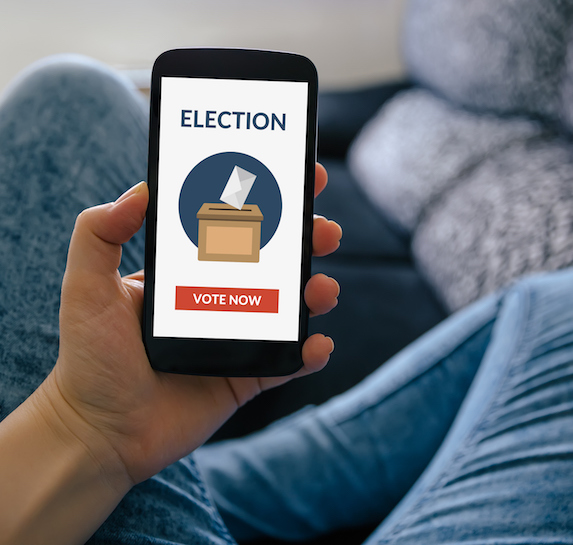 A person sits holding a phone with a voting app open on the screen