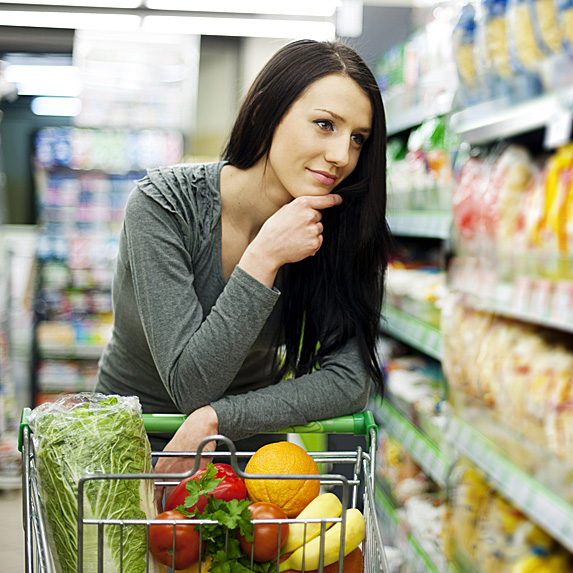 Woman walking down aisle with grocery cart