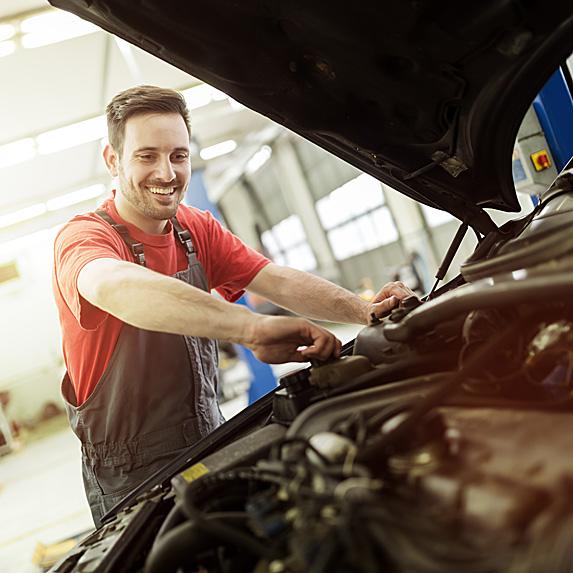Mechanic fixing something under hood of car