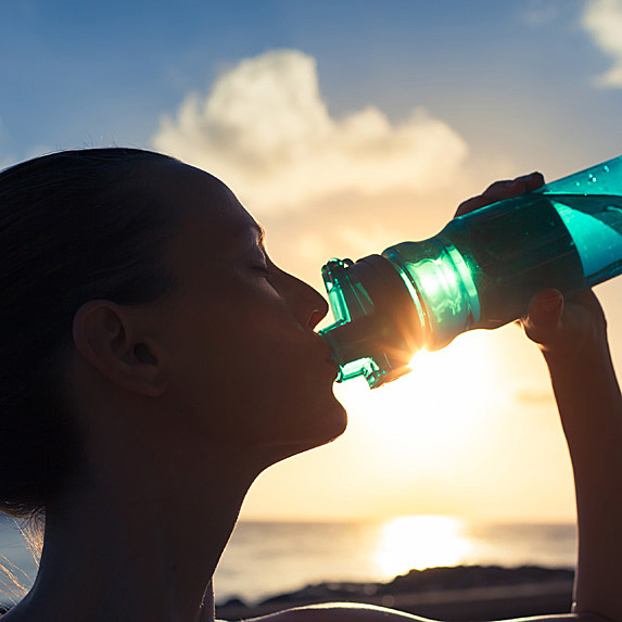 Woman drinking from refillable water bottle