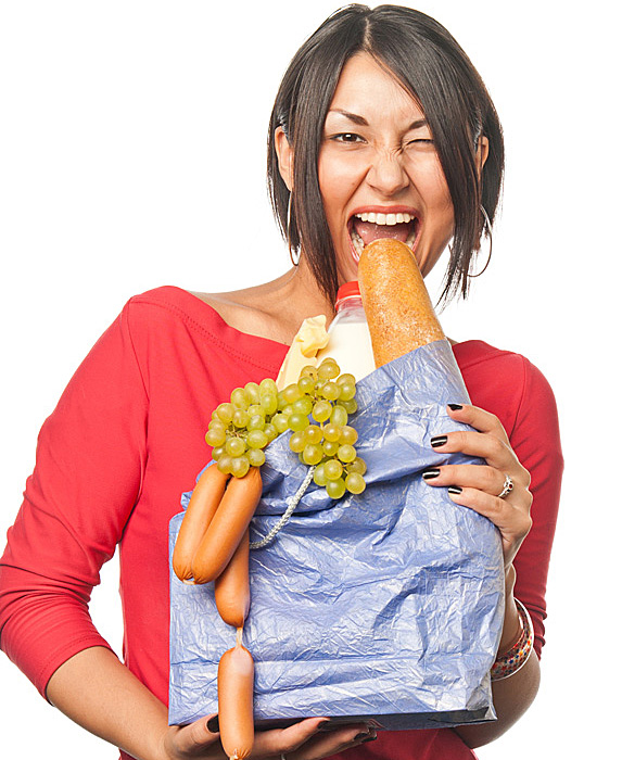 Woman biting bread straight out of shopping bag