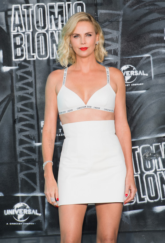 Charlie Theron wears a white bikini-style top and co-ordinating white mini skirt to a film premiere