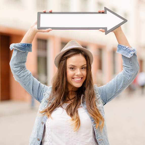 A young smiling woman in a hat holds up an arrow symbol