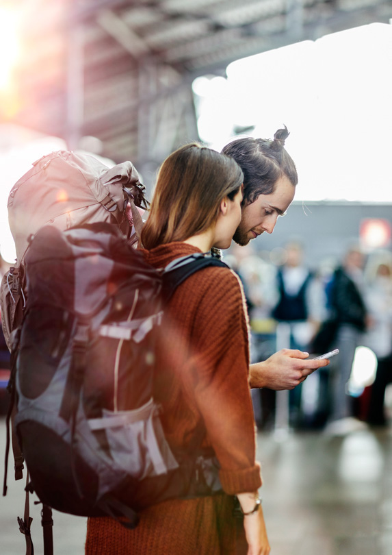 A young couple traveling looks down at the phone in the man's hand